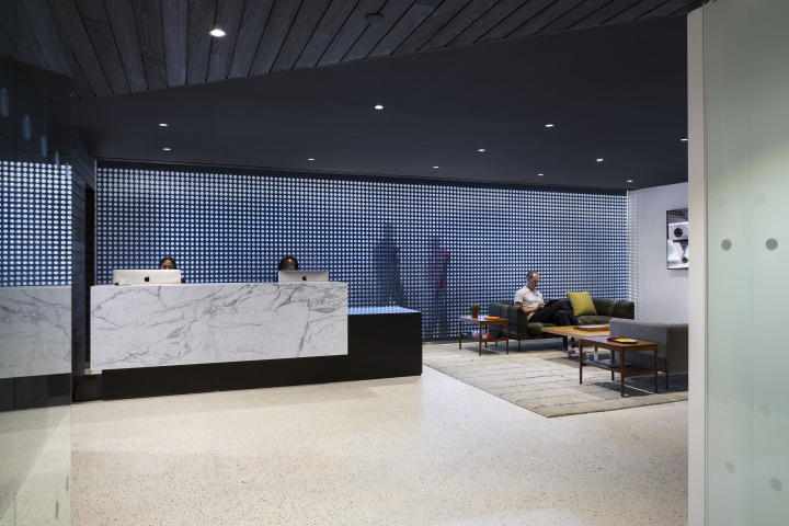 The reception area. The custom installation behind the desk separates the work area and is fabricated with multi-ply felt panels and grid glass inserts that recall the glass bullet sidewalks of SoHo, where Droga5 used to be located.