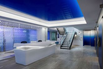 The new workplace design includes several custom-designed pieces, such as this wave-like reception desk. Image courtesy of