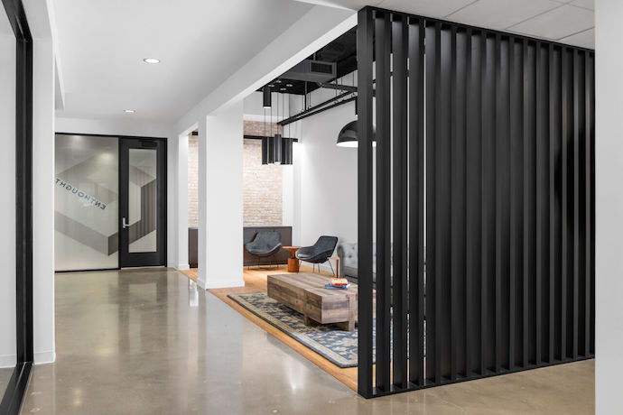 The entry way is finished by a backdrop of floor-to-ceiling black reclaimed wood slats. Image courtesy of Peter Molick.