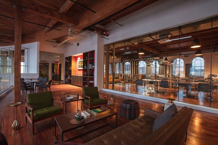 This renovation preserves the classic Warehouse District architecture of the existing building while incorporating modern elements. The light-filled space features high ceilings with exposed beams, large windows, a contemporary art collection, and a flowing, open floor plan. Image courtesy of Neil Alexander.